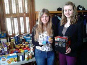 Kaitlin Sherber and Grace Butler help organize food donations